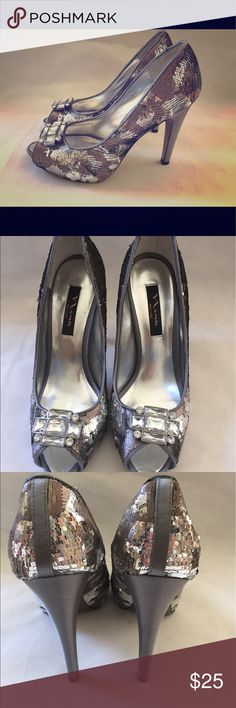 Nina New York Sparkle Peep Toe Pumps Silver Size 9 Shoes are in very good condition.The back of one of the heels have two scoff marks.Also inside back of heel has some discoloration.It comes with the original soft pink carrying bag and box.Box has tears on corners of the lid. Nina Shoes Heels
