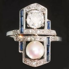 An impressive engagement ring featuring 1.05 carat diamond and one pearl surrounded by blue sapphires, platinum shank, crafted circa 1920s, Art Deco period, engagement ring in excellent condition... A touch of history.