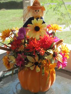 make your own pumpkin arrangement.  Pumpkin from Wal Mart; cut into the top and set aside; poke in your fall flowers and add a dollar scarecrow and a bow.  Using a floral pin place lid of pumpkin on the back.  EASY