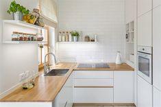 Kuchyňská linka je vyrobená na míru v bílém matném laku. Zajímavě jsou řešené úchytky, jež tvoří součást dvířek. Pracovní deska je z masivního dubu stejně jako zakázkově vyrobený jídelní stůl. Plochu podlahy rozšířil velký formát dlažby imitující přírodní mramor.