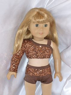 """It is a two piece outfit. The bodice is made of a lined brown """"squiggle"""" sequins lycra fabric. It has one sleeve and one strap. There is a back velcro closure. The boy shorts are made of brown sequin lycra and brown lycra."""