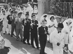 [AHS 62769]    Communion Class, n.d.    Most of the local Mexican American community affiliated itself closely with Catholicism, some attending Saint Augustine Cathedral. This image captures young boys and girls entering the church as they embark on a major religious milestone, their first Holy Communion. This event was usually followed by a celebration at each child's home.