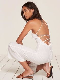 How to wear clothes without feeling like you're wearing clothes. This is an open back jumpsuit with cross-back strap details, a sweetheart neckline and a slightly cropped leg.