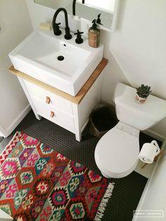 Коврик на полу отлично оживляет безликий интерьер ванной.