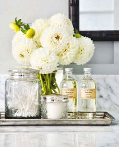Using pretty everyday items such as a silver tray and glass containers, elevate ordinary bathroom items. From Lexi's Ultimate Bathroom Organization Tips