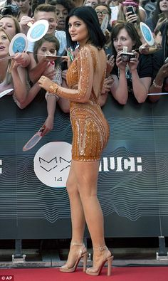 Golden girl: Kylie Jenner, 16, stood out in her bright orange sequinned optical illusion m...