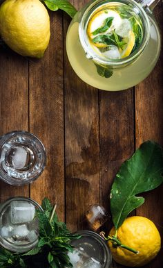 #Jug with homemade lemonade  Jug full of homemade lemonade with mint slices of lemon and ice cubes served with fresh lemons and mint over wooden background top view vertical composition copy space