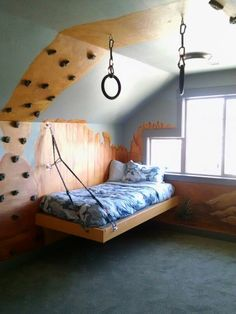 Great rock climbing themed room. The platform bed is suspended with rope and carabineers. The walls are painted with a beautiful Southern Utah scene. And just for fun, gymnastics rings hang from the ceiling.