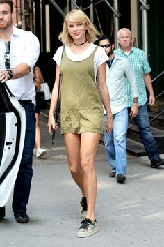 Taylor Swift wears a white tee underneath an olive khaki romper with sneakers