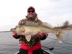 Walleye caught on handmade lure in fisherman's hand against clou
