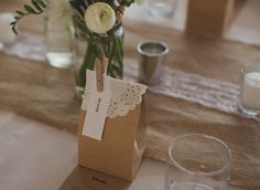 """""""Our place cards doubled up as wedding favours which were also DIY. They were little brown paper bags filled with macarons and sealed with white paper doilies and small wooden pegs. Even though I was putting them together the night before and morning of the wedding, they were a lot of fun! Also, we were so incredibly lucky that my brother who is an amazing graphic designer helped create our invites, ceremony programs and menu cards."""""""