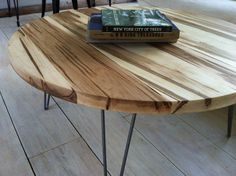 Round coffee table, mid century modern style featuring wormy maple top and hairpin legs.