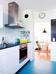 A streamlined kitchen with lots of storage space. Cabinets with a black composite worktop, Kvik. Notice board painted onto the wall with chalkboard paint.