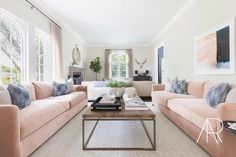 Alyssa Rosenheck - Amanda Barnes Interior Design - Contemporary living room features two pink velvet sofas lined with gray and blue pillows facing each other across from a metal and wood coffee table.