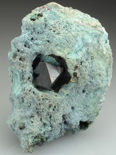 A fine euhdral crystal of Cuprite from the classic Kolwezi mining area DR of Congo, the specimen we have to offer comes from the Dikuluwe Mine. An octahedral crystal measuring to 1.4cm sits centre stage in a cavity in the matrix.