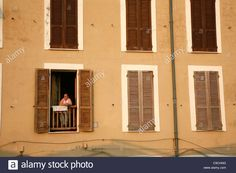 Download this stock image: Woman standing in her window at a house built along the city walls. Alghero, Sardinia, Italy. - C9CHNG from Alamy's library of millions of high resolution stock photos, illustrations and vectors.