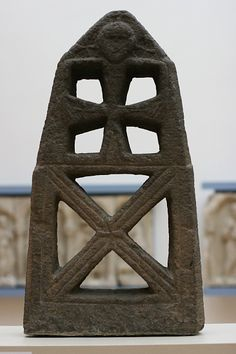 The Moselkern Stele is one of the most puzzling (and fascinating) objects in the Rheinischen Landesmuseum's collection. It was found in 1915 in a cemetery near Moselkern (Kreis Cochem-Zell). The stone is believed to have been made in a Rhenish workshop in the 7th century AD.    That it is a Christian monument is certain. In the upper section a Crucifix is carved out; above it appears a large human face and arms, which wrap around the cross and seem to hold the hands of the crucified Christ.