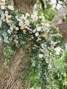 pretty ceremony garland in tree with green and white blooms.