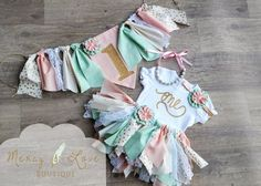 The Amelia Fabric Tutu Collection from Mercy & Love Boutique: -Bubblegum Necklace: Light Pinks, Whites, Pearl and Mint Beads -Headband: Mint and Pink Fabric Flower Stretchy Headband (If you prefer Alligator Clip...please note during checkout) -The Amelia Tutu: A Fabulous Scrappy Fabric Tutu with beautiful modern vintage theme! It features various shades of sea foam green, pink, cream, gold and white lace. Looks great with boots and cuffs or leggings in Fall and Winter months too! I take…