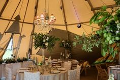 Internal photo of three of our giant hat tipis. Layout with round tables - Image by Sarah Vivienne Photography