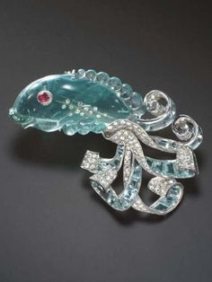 AN AMUSING ART DECO AQUAMARINE, DIAMOND AND RUBY BROOCH. The carved aquamarine fish, with a cabochon ruby eye and single-cut diamond detail, extending a scrolling pavé-set diamond and calibré-cut aquamarine tail, mounted in platinum,  circa 1935. #ArtDeco #brooch