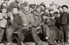 Two of Harold Giedt's Navy and Marine enlisted friends sitting in a crowd of friendly local children for a group photograph in a Tientsin park, 1946. Harold Giedt Photograph Collection.