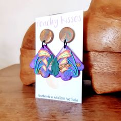 Made with a silk screen print base with 3D jungle leaf features in purple, forest green and hints of metallic gold, these gorgeous statement earrings by Peachy Kisses Handmade will brighten up any outfit! ~*~ #peachykisseshandmade #earrings #handmadeearrings #polymerclayearrings #handmadejewellery #handcraftedjewellery #earrings #earringsoftheday #statementearrings #earcandy #earringstyle #earringaddict #earringlover #earringshandmade #earringaddiction Handmade Jewellery, Handcrafted Jewelry, Earrings Handmade, Handmade Items, Unique Jewelry, Statement Earrings, Drop Earrings, Large Fan, Silk Screen Printing