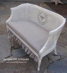 A beautiful French wicker settee painted in chalk paint, upholstered in linen with a detachable ruffle and bee stencil.