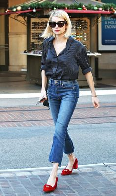 Emma Roberts adds a polished touch to her raw hem cropped flares with a button-down blouse and chic red block heels.