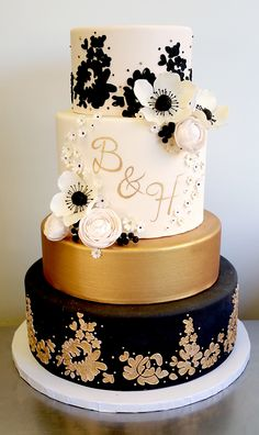 Black, gold, and blush lace monogramed wedding cake with gum paste ranunculus and anemone flowers (4-tier, fondant)