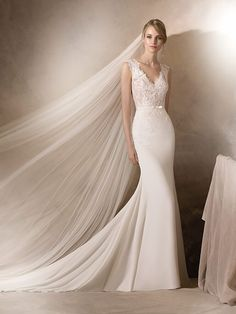 HALDISA | Pronovias  Delicate mermaid style wedding dress in . A V-neckline and lace details over the hips make this a fabulously feminine dress