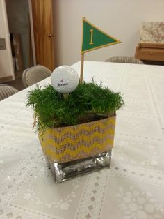Easy peasy. Turf (if it's not sod time we'll use wheat grass and cut it short), vase, ball, tee and flag number.