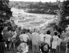Onlookers gather to watch the flood waters of the James River near the south end of of the Lee Bridge in Richmond. The James River peaked at 28.6 ft in Richmond from Hurricane Camille. 8/21/1969. No. 69-2051, Virginia Governor's Negative Collection, Library of Virginia.