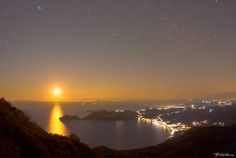 Chelidonofolia nightscape view - Chelidonofolia nightscape view  Night landscape view from Kratsalo mountain of Corfu, with the setting Moon above Agios Georgios beach of north.  With souther leg of Italy just under the Moon and the moonlight fading through Porto Timone peninsula. On the top right we can see the sitting in the heavens tied to a chair, Queen Cassiopeia. While on the top left are the seven sisters of Atlas and Pleione. Under The Moon, Corfu, Heavens, Moonlight, Sisters, Mountain, Italy, Queen, Sunset