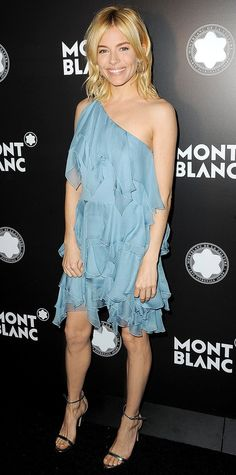 Sienna Miller a powder blue one-shoulder ruffled dress, complete with gold hoops and metallic sandals.