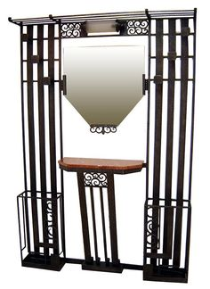 Large French Art Deco hand wrought iron hall tree / 1930's /  Features a hat rack across the top, six coat hooks, a light, two umbrella/cane holders and a marble shelf for keys and change.