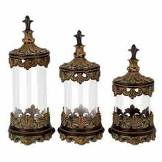 """Set of 3 glass canisters with openwork acanthus leaf accents.      Product: Small, medium and large lidded canisterConstruction Material: Resin and glassColor: Brown and clearDimensions:  Small: 13"""" H x 6"""" Diameter  Medium: 15"""" H x 6"""" Diameter Large: 17"""" H x 6"""" Diameter"""