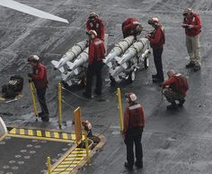 GULF OF OMAN (June 14, 2013) – Sailors move ordnance across the flight deck on board the aircraft carrier USS Nimitz (CVN 68). Nimitz Strike Group is deployed to the U.S. 5th Fleet area of responsibility conducting maritime security operations, theater security cooperation efforts and support missions for Operation Enduring Freedom.(U.S. Navy photo by Mass Communication Specialist Seaman Apprentice Kelly M. Agee/ Released)