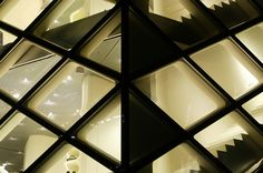 Prada Store in Tokyo by Herzog & de Meuron-the bubble glass exterior walls emit a warm glow through their diamond frames.  The black stairs also create a contest with the illuminated sales area.