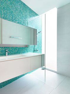 13 Inspirational Examples Of Blue And White Bathrooms // An accent wall of aqua blue tiles in this bathroom adds color and a focal point, as well as helps to create a relaxing little oasis.