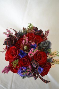 Unique sottish-inspired bridal bouquet with roses, thistle, heather, cornflower and leukadendron. Fleurish Floral Designs