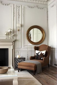 I love the traditional detail on the walls and trim along the ceiling mixed in with the clean lines of the coffee table and the pillow and side table next to the chair - it makes me want to plop down and read a book.