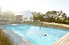 Girlfriends lounging by pool in summer of luxury modern design farmhouse in Sonoma, California