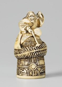 An ivory netsuke of Kiyohime atop the Dôjôji bell. 19th century