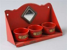 """Rood miniatuur wandrekje met drie voorraadbakjes met opschrift """"zand"""", """"zeep"""" en """"soda"""", op achterplaat een spiegeltje"""