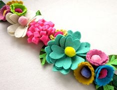 The bright colors of these felt flowers on this garland are perfect for a little girl's bedroom or nursery Faux Flowers, Diy Flowers, Fabric Flowers, Paper Flowers, Felt Headband, Felt Garland, Flower Garlands, Diy Crafts, Arts And Crafts