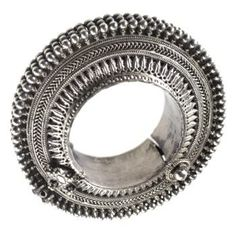Annular silver anklet with hinged segment, the periphery composed of three rows of pellets, with ring of bands of plaited wire, and chased foliations and beads: India, Punjab