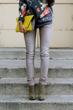 Gray ankle boots, gray skinny jeans, printed sweatshirt, and a pop of colour in the clutch