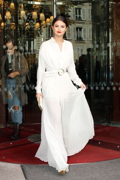 A belted white maxi dress, red lip and slicked back hair is such a chic look for Selena Gomez