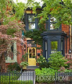Toronto interior designer Jeffery Douglas offset this home's deep black trim with a golden yellow door — a traditional Victorian accent that lifts and brightens the black. The lush garden and wrought-iron fence supply even more charm. Victorian Front Garden, Victorian Front Doors, Victorian Terrace House, Victorian Homes, Edwardian House, Antique Doors, Terrace House Exterior, Townhouse Exterior, Exterior House Colors